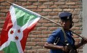A policewoman carries a Burundi flag during a protest against President Pierre Nkurunziza's decision to run for a third term in Bujumbura, Burundi, May 29, 2015.