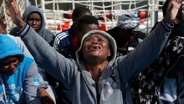 A tearful migrant prays on a Migrant Offshore Aid Station ship after being rescued around 20 nautical miles off the coast of Libya, June 23, 2016.