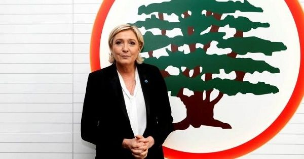 Marine Le Pen stands in front of the logo of the Christian Lebanese Forces party, Maarab, Lebanon Feb. 21, 2017.