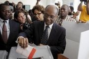 File photo from 2015 depicting Aristide dropping his ballot in an electoral bin at a polling station in Port-au-Prince.