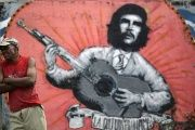 A man stands next to a mural of Ernesto 'Che' Guevara