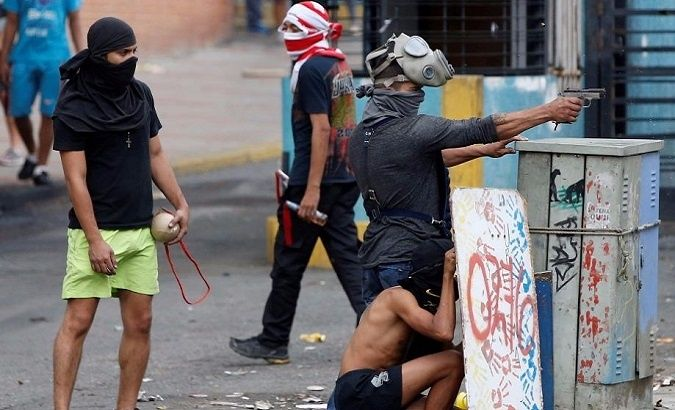 A demonstrator aims a pistol during clashes with government forces as the Constituent Assembly election was being carried out in Caracas, Venezuela, July 30, 2017