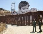 The boy glances down from the Mexican side at two Border Patrol officers in the United States.