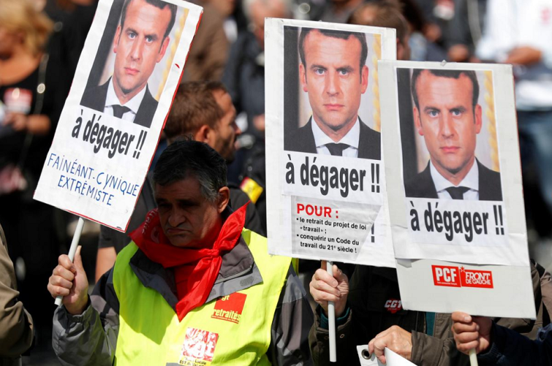 "Demonstrators hold placards with portraits of French President Emmanuel Macron and the slogan ""To clear out"" during a national strike and protest against the government"