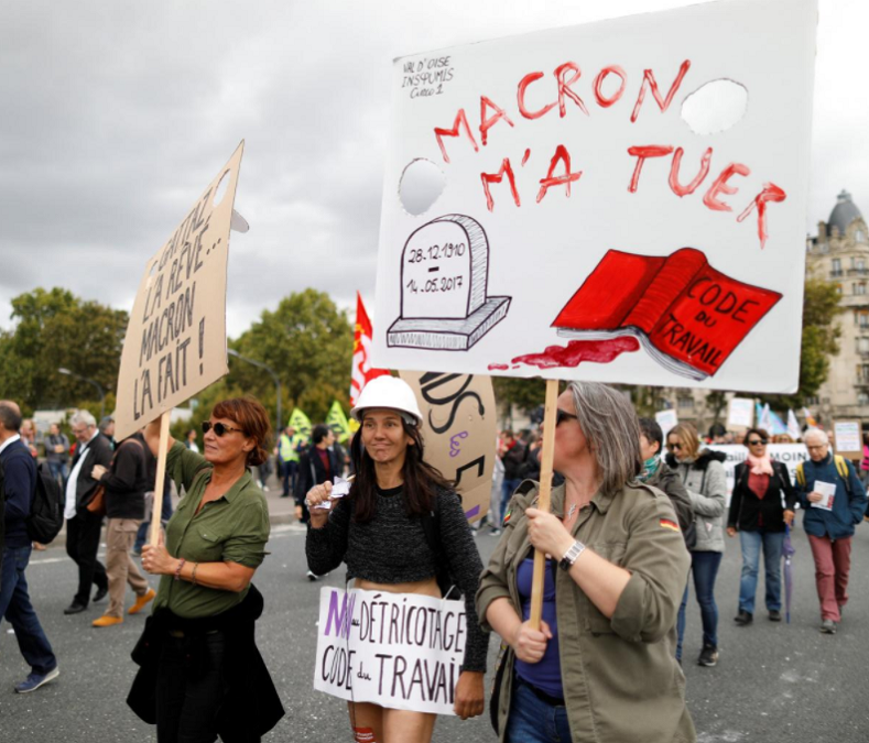"A demonstrator holds a placard that reads ""French President Emmanuel Macron killed me"" during a national strike and protest against the government"