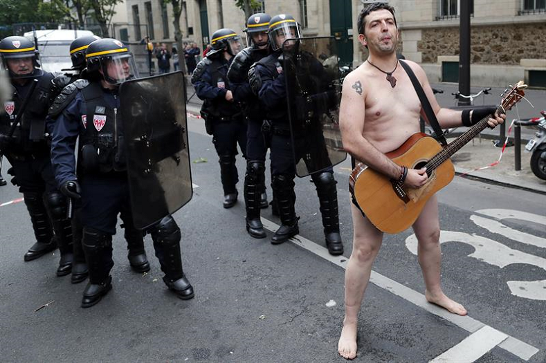 A naked protester plays his guitar in front of several riot police during a first day of strikes and protests against a labor reform decree by French President Emmanuel Macron on September 12, 2017.