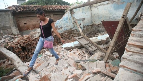 Peregrina Vera, an Zapotec muxe walks on the debris of her house destroyed after an earthquake in Juchitan, Mexico.