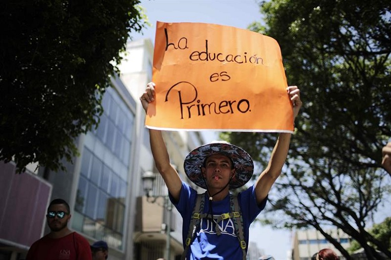 "A protester holds a sign reading ""education comes first"" at a protest in San Jose on September 12, 2017."