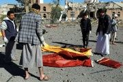 Yemenis collect the corpses of people killed in Saudi airstrike in Sana'a