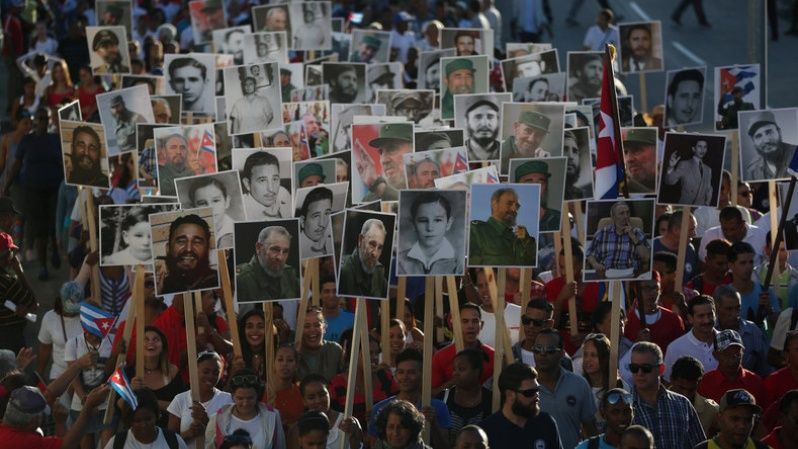 People carry images of late Cuban President Fidel Castro during a march to Santa Ifigenia Cemetery to commemorate the first anniversary of interment of Castro
