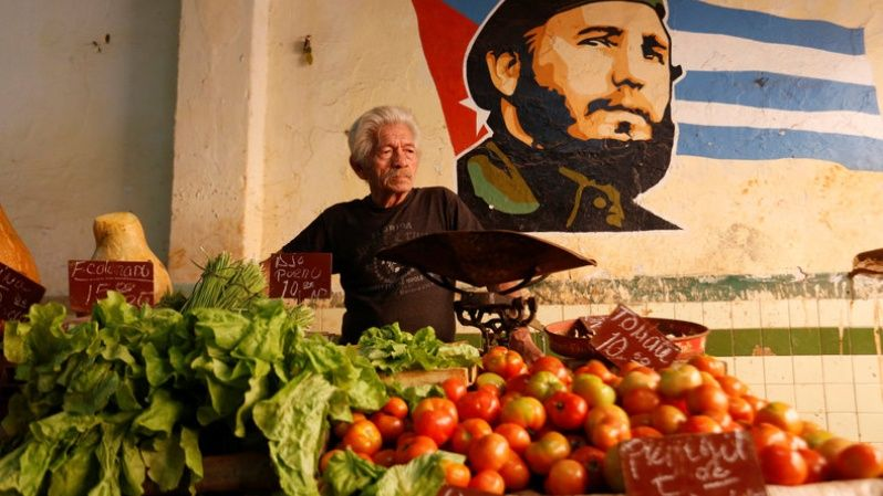 A man waits for clients inside a private vegetable market, next to an image of Cuba