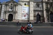 People on a motorcycle ride past Lima Cathedral with a banner of Pope Francis prior to his visit to Peru, scheduled to follow his tour of Chile.