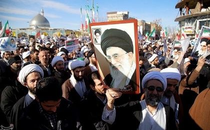 Pro-government counter-protesters hoist pictures of Supreme Leader Ayatollah Ali Khamenei.