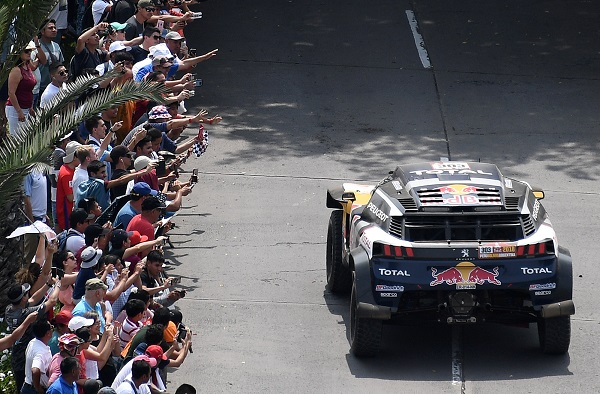 Crowds wave at Peugeot Total driver Sebastien Loeb and copilot Daniel Elena.