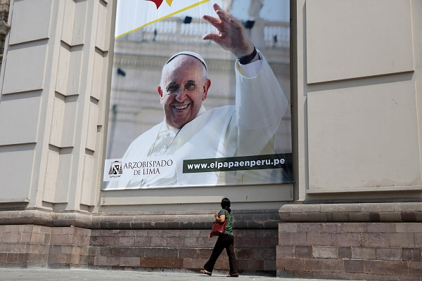 A woman walks past Lima Cathedral with a banner of Pope Francis prior to his visit to Peru.