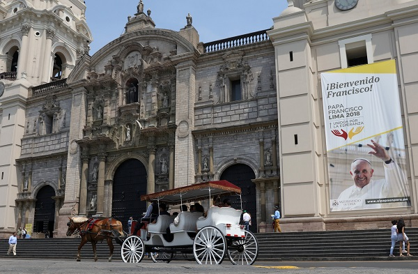 People ride in a horse-drawn carriage past Lima Cathedral and a banner of Pope Francis.