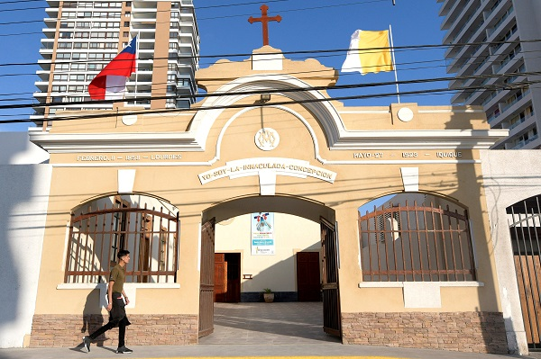 A citizen walks past a church decorated with the flags of Chile and the Vatican ahead of the papal visit in Iquique, Chile.