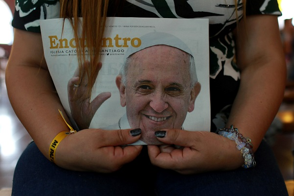 An inmate holds an image of Pope Francis before a choir of female prisoners who will perform for the pontiff in Santiago, Chile.