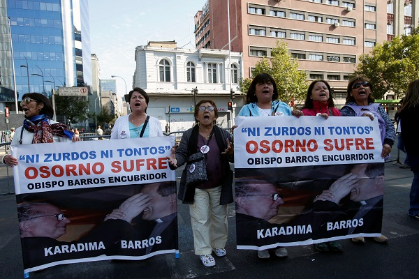 "Protesters against sex abuse in the Catholic church hold banners reading ""Neither lefties nor fools, Osorno suffers, Bishop Barros, accessory after the fact."""