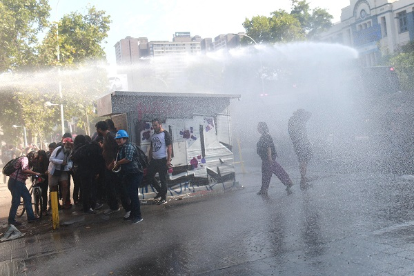 Demonstrators take cover from a police water canon during a protest against the papal visit in Santiago.