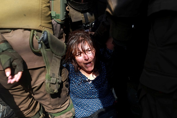 A woman is detained during a protest against the papal visit in Santiago.