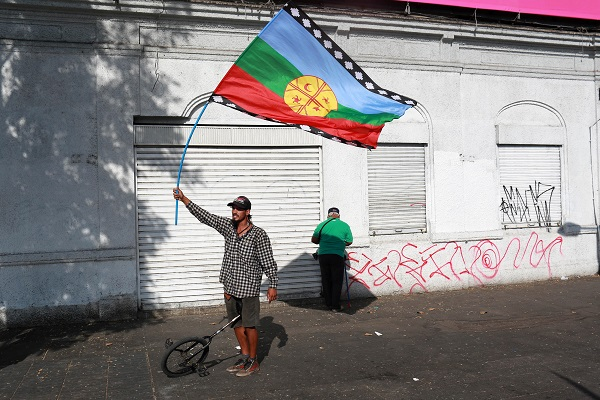A demonstrator holds up a Mapuche Indian flag during a protest against the papal visit in Santiago.