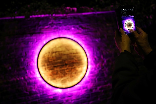 "A visitor takes a photograph on their mobile phone of ""Harmonic Portal,"" by Chris Plant."
