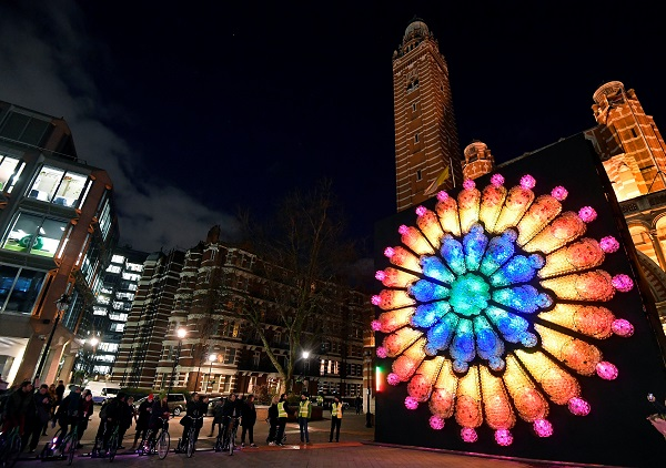 "People ride bicycles to generate the electricity to illuminate ""The Rose,"" by Mick Stephenson, outside Westminster Cathedral."