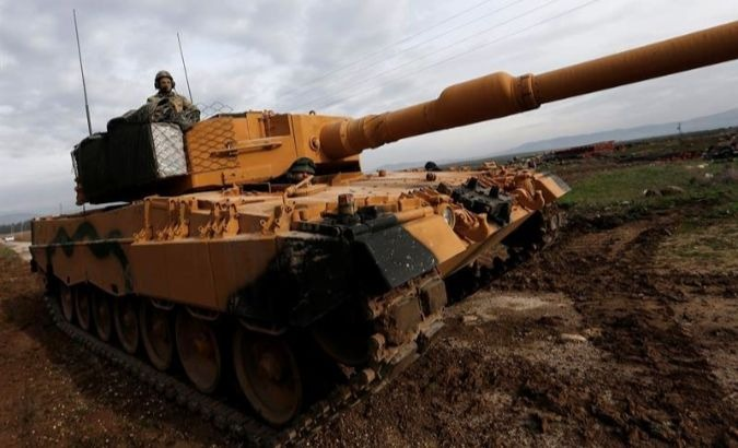 A Turkish soldier sits on a tank as Turkish troops prepare near the Syrian-Turkish border at Reyhanli district in Hatay, Turkey.