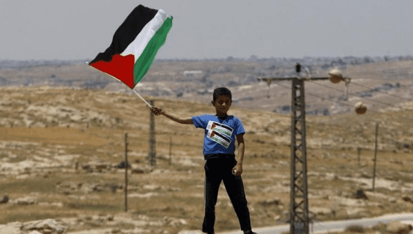 A Palestinian Bedouin boy holds a Palestinian flag during a protest against Jewish settlements in Susya village south of the West Bank city of Hebron June 5, 2015.