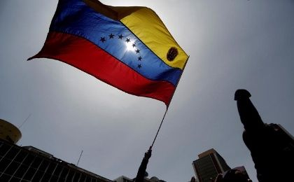A pro-government protester holds a Venezuelan flag.