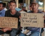 Venezuelan migrants hold placards looking for work in the Brazilian city of Boa Vista.