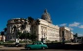 A vintage car drives in front of the Capitol building in Havana