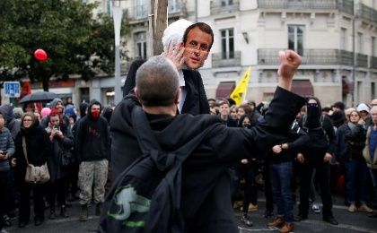 A protester punches a dummy depicting French President Emmanuel Macron in Nantes, France.
