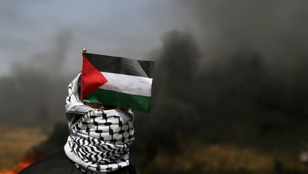 A demonstrator with a Palestinian flag looks on during clashes with Israeli troops at a protest demanding the right to return to their homeland, in the southern Gaza.