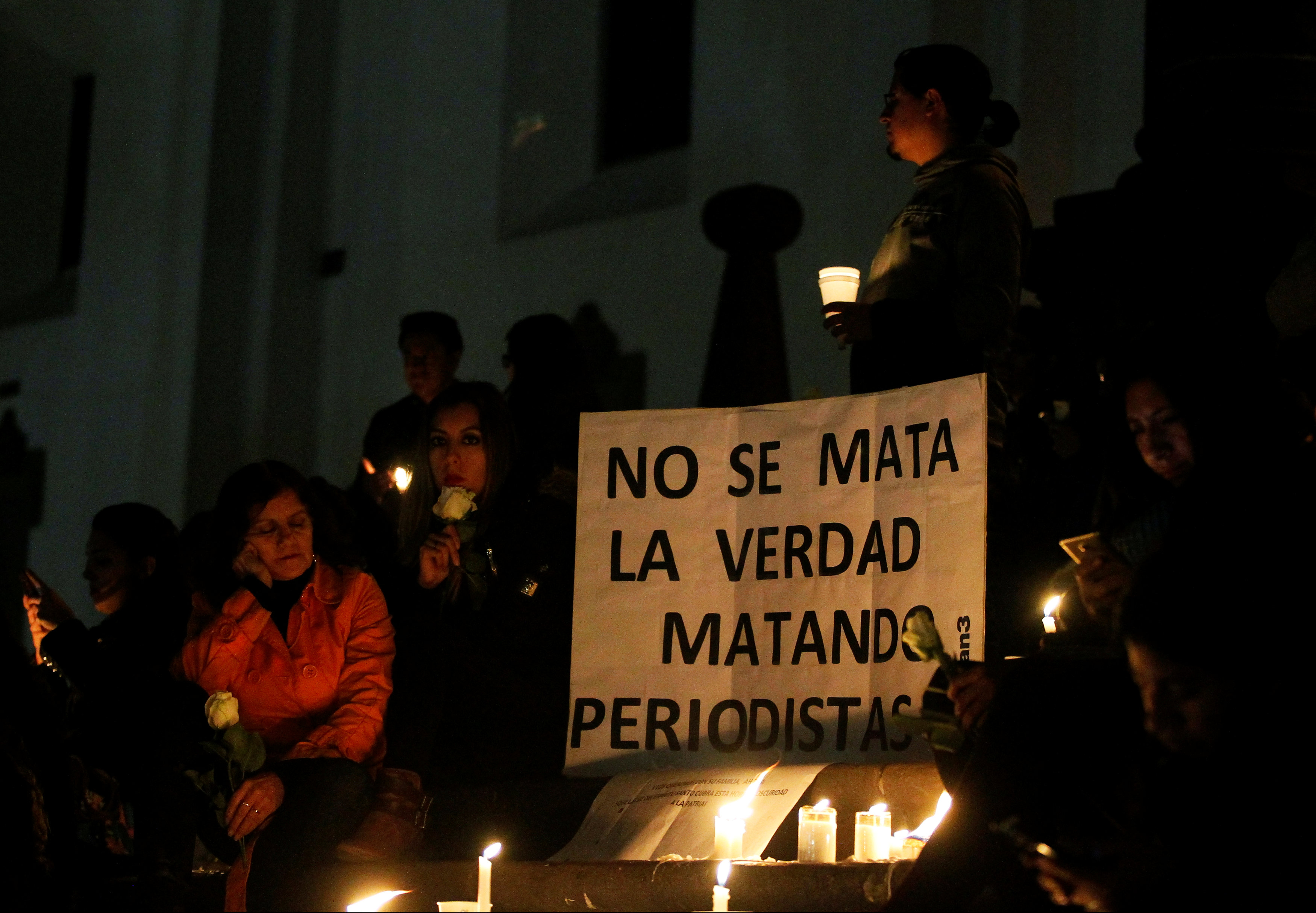 People participate in a vigil for two Ecuadorean journalists and their driver in Quito, Ecuador April 13, 2018. The sign reads,