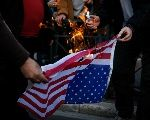 Protesters burn an U.S. flag during a demonstration outside the U.S. embassy against air strikes carried out in Syria, in Athens, Greece, April 14, 2018.