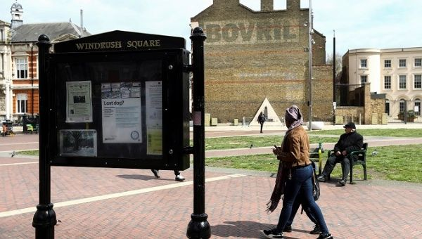 People walk past a sign on Windrush Square in the Brixton district of London, Britain April 16, 2018.