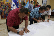 Transporation leaders sign accord with the government to increase tax, van and bus fares across Honduras. July 31, 2018.