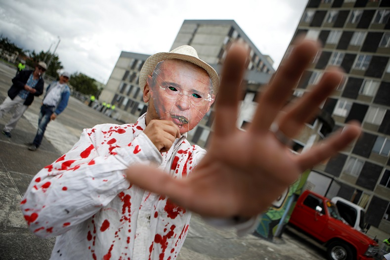 A protester wears a mask of former President Alvaro Uribe and a bloodied shirt. Uribe is expected to play an important role in the Duque government.