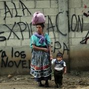 "A Mayan indigenous woman and her son in front of a graffiti that reads ""No To Mine Exploration"" while waiting for the UN special rapporteur on indigenous rights James Anaya in San Juan Sacatepequez. June 15, 2010"