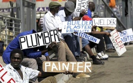 Men hold placards offering temporal employment services in Glenvista, south of Johannesburg.