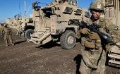 US army soldiers stand next to military vehicles in the town of Bartella, east of Mosul, Iraq.