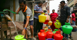 A man uses a hand-pump to fill up a container with drinking water as others wait in a queue on a street in Chennai, India, June 17, 2019.