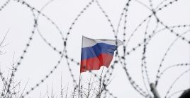 Russian flag is seen through barbed wire on the roof of the Russian embassy in Kiev, Ukraine, March 26, 2018.