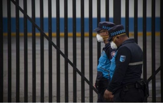 Security personnel wearing face masks walk past a hospital in Quito, Ecuador, March 17, 2020.