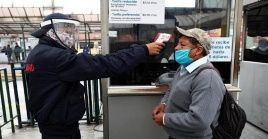 Workers perform body temperature tests on citizens using public transports in Quito, Ecuador, on June 3, 2020.