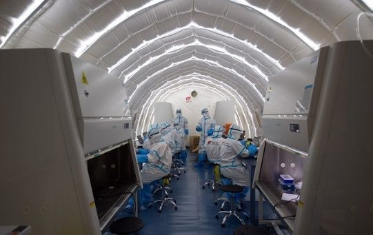 Staff members work in an inflatable COVID-19 testing lab in Beijing, China, June 23, 2020.