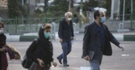 People wearing face masks cross a street in Tehran, Iran, Oct. 21, 2020.